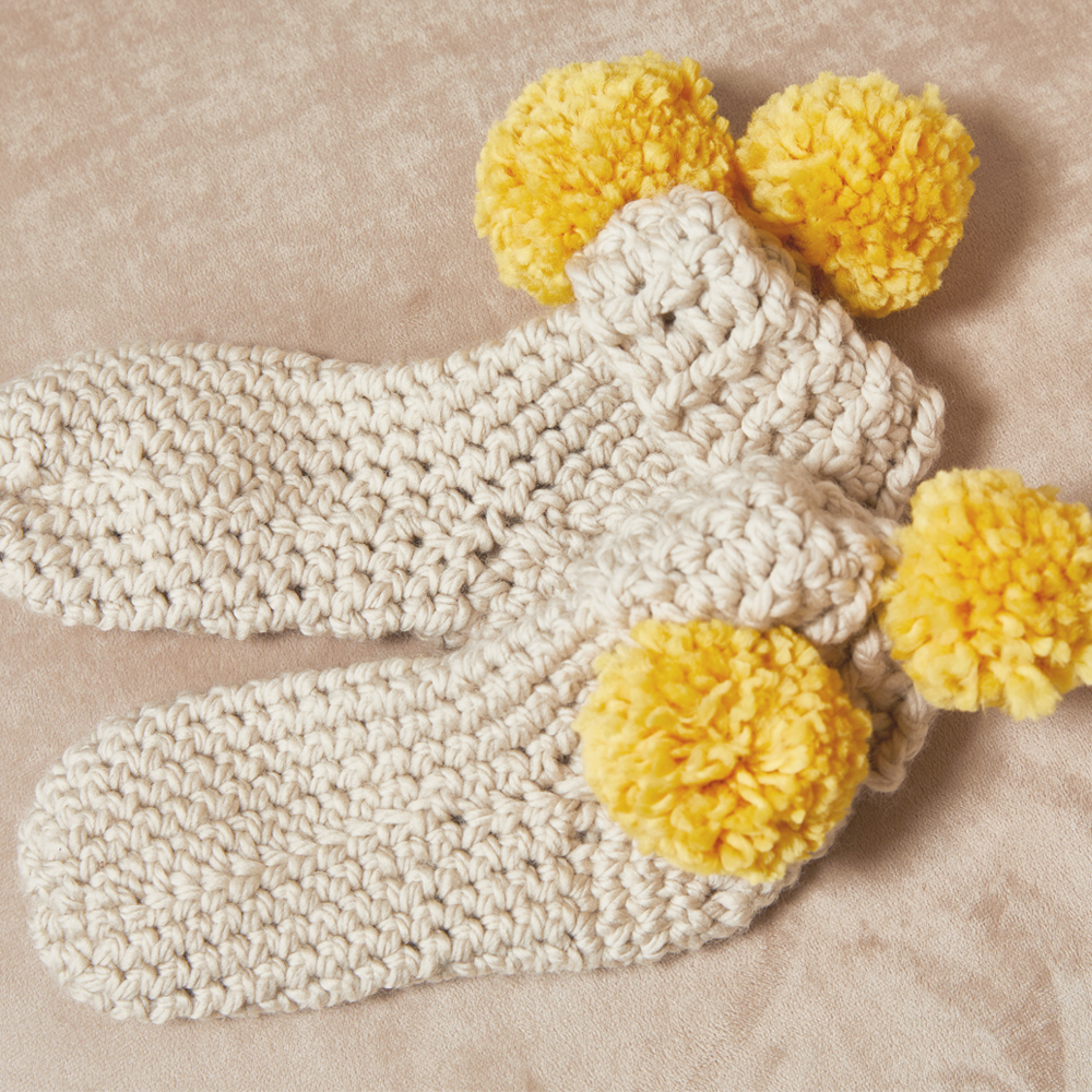 If you're looking for a cozy little gift for someone small, the Pom Pom Slippers are the cutest gift around. #crochetslippers #crochetpattern #crochetlove #crochetaddict