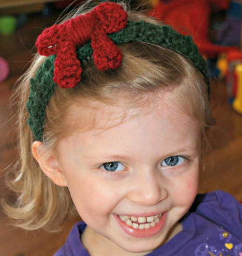 Holiday Wreath Headband - This list of unique crochet baby headbands for girls are sweet and simple. You can whip these free crochet patterns up in no time, and there are so many options. #CrochetBabyHeadbands #BabyHeadbandPatterns #FreeCrochetPattern