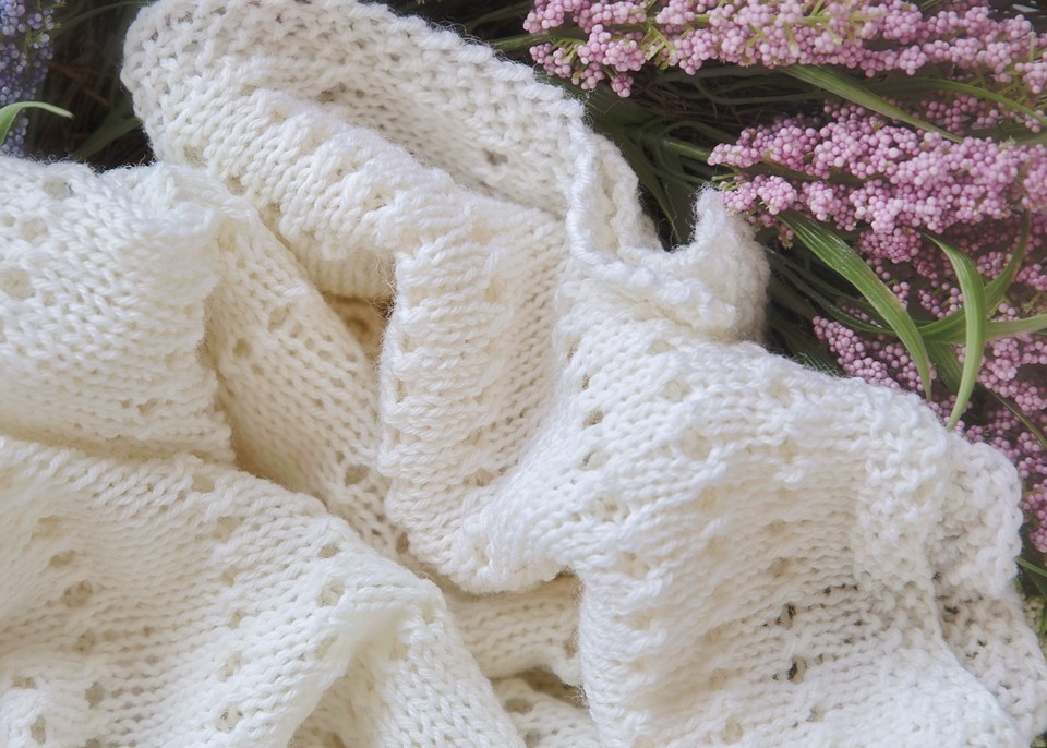 Eyelet Baby Blanket - Each of these baby blanket knitting patterns is suitable for any skill level and is fun to make. The best part is how colorful they all are and how versatile. #BabyBlanketKnittingPatterns #KnitBabyBlankets #FreeKnitPatterns