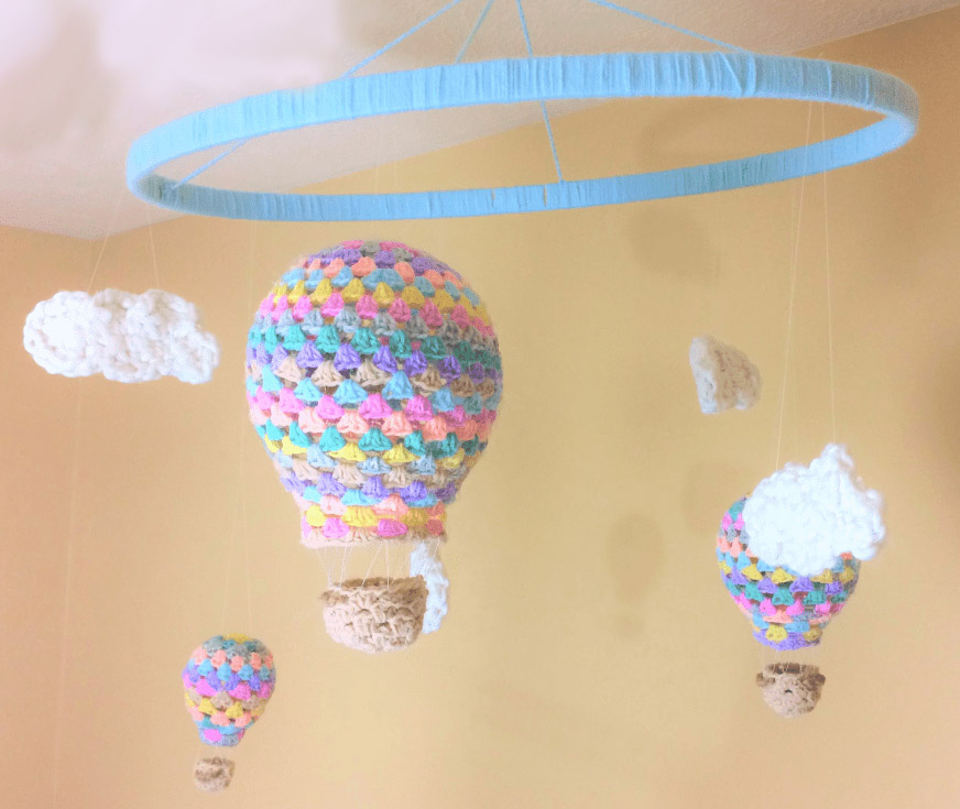 Hot Air Balloon Nursery Mobile - Crochet baby mobiles are colorful, fun and creative. Grab your hook and your favorite type of yarn, and get started on a baby mobile for someone you know. #CrochetBabyMobiles #CrochetPatterns #FreeCrochetPatterns