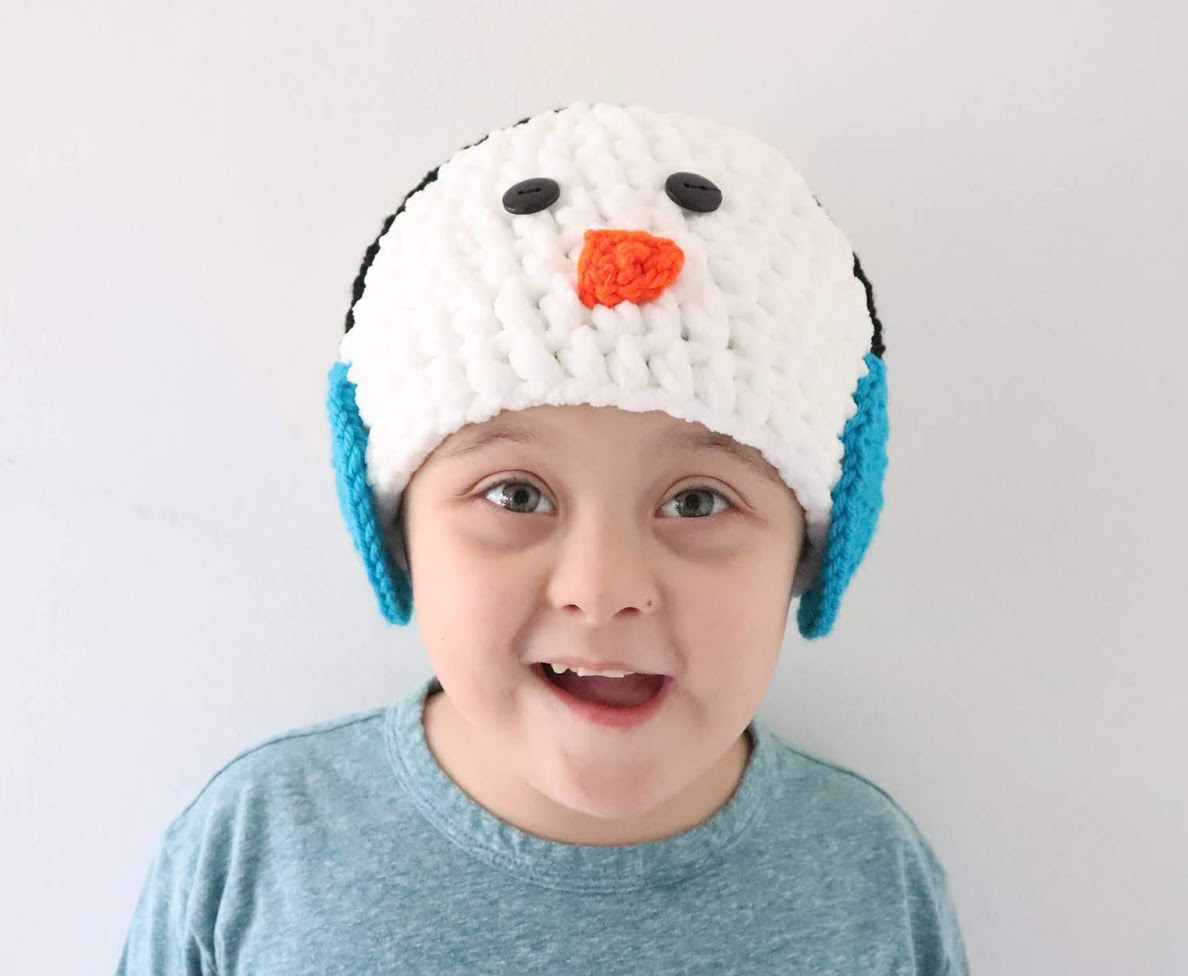 Snowman Hat With Earmuffs - This list of Christmas Crochet hat patterns will supply you with anything from the classics (Santa, Rudolph, Snowman) to fun animals and well-loved characters. #ChristmasCrochetHatPatterns #CrochetHatPatterns #CrochetPatterns